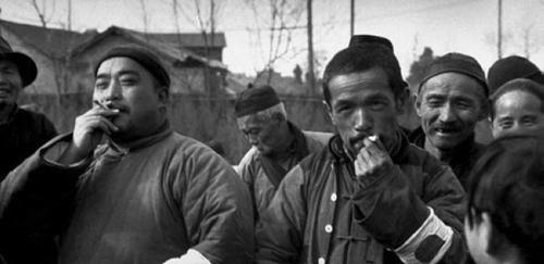 """两个手臂上带着""""太阳旗""""袖标的中国人惬意地抽着香烟,而周围的围观者则投以羡慕的眼神。-图片版权归原作者所有"""