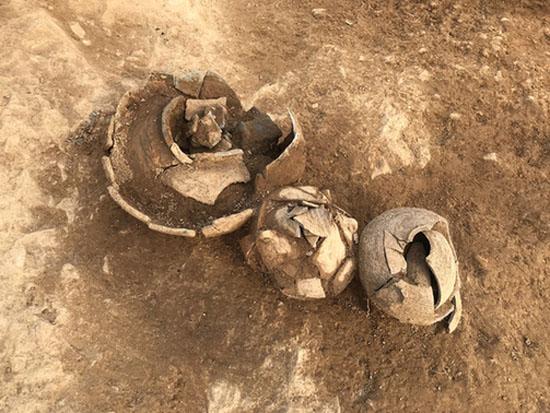 茗山挖掘现场,考古队员挖出几个陶罐。-图片版权归原作者所有